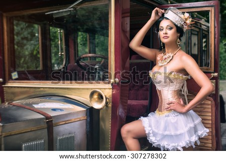 Portrait of a sexy beautiful woman posing over retro car. Cabaret and pin-up concept. - stock photo