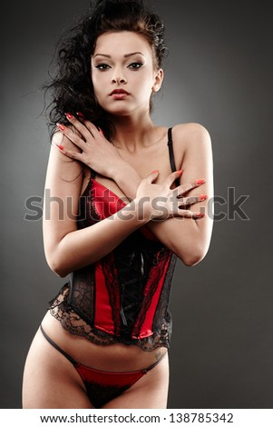 Portrait of a sexy brunette wearing negligee on gray background - stock photo