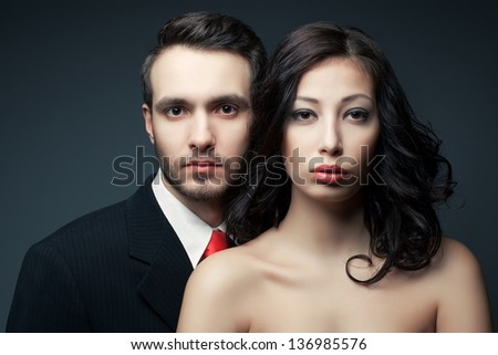 Portrait of a sexy couple, beautiful young man and woman posing over dark gray background. Classic style. Perfect hair and skin. Close up. Studio shot. - stock photo