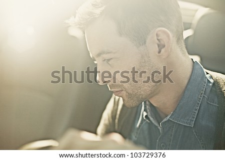 Portrait of a sexy fashion man in the car - stock photo
