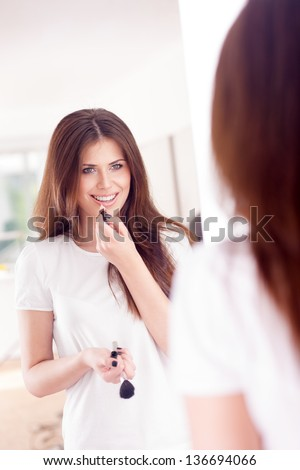 Portrait of a sexy girl putting makeup, looks in the mirror