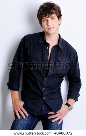 Portrait of a sexy handsome young man posing in the studio with modern curly hairstyle - stock photo