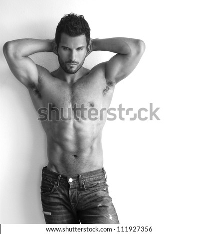 Portrait of a sexy muscular male model against white background with copy space