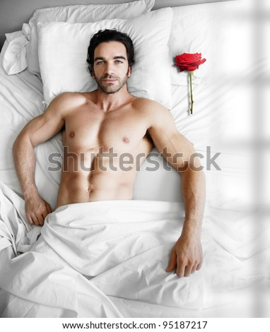 Portrait of a sexy muscular male model waiting in modern bed with single red rose on pillow - stock photo