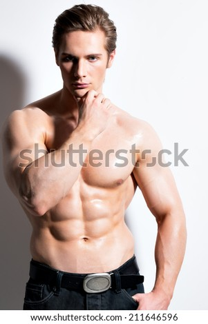Portrait of a sexy muscular young man posing on a white background with contrast shadows.