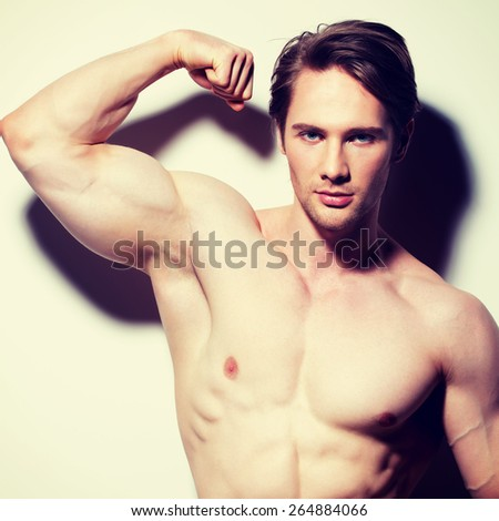 Portrait of a sexy muscular young man posing on a white background with contrast shadows. - stock photo
