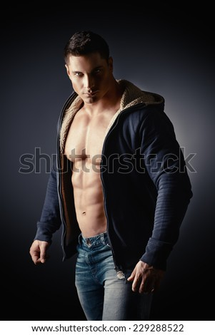 Portrait of a sexy muscular young man posing over dark  background. - stock photo