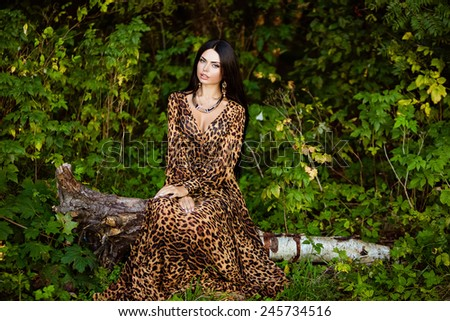 Portrait of a sexy sensual very beautiful brunette girl with long hair in leopard print dress, sitting on a tree in a forest
