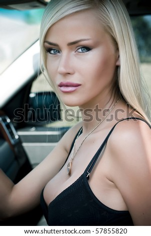 Portrait of a sexy woman in  car - stock photo