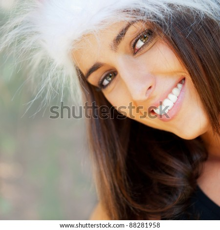 Portrait of a sexy young female smiling in a park and looking at camera wearing elegant dress and christmas Santa Claus hat. Happy New Year on vacation at Warm Country