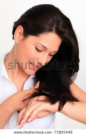 Portrait of a sexy young lady looking confidently and arranging her hair - stock photo