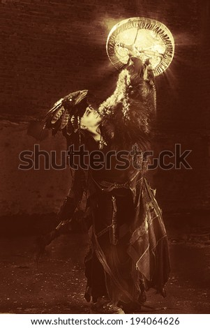 Portrait of a shaman dancing with a drum outdoor.  - stock photo