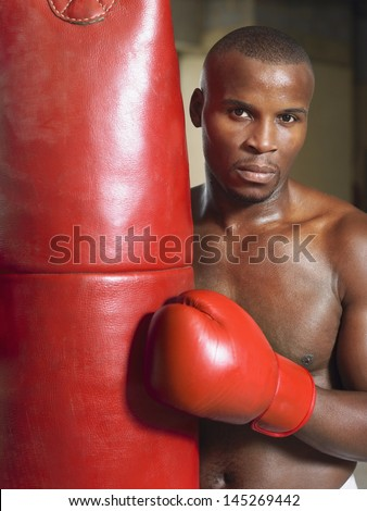 Portrait of a shirtless African American boxer with punching bag - stock photo
