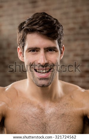 Portrait of a shirtless man smiling at the gym - stock photo