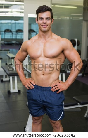 Portrait of a shirtless muscular man posing in gym