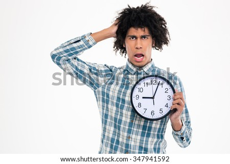 Portrait of a shocked afro american man holding wall clock isolated on a white background