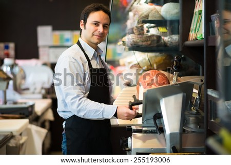 Portrait of a shopkeeper at work in a grocery store - stock photo