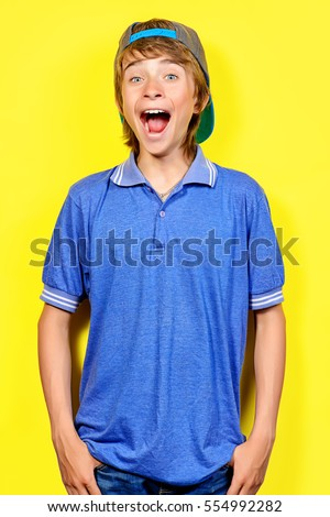 Portrait of a shouting teenage boy over yellow background. Studio shot. Teenager awkward age.