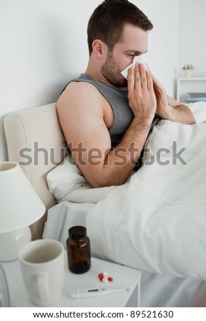 Portrait of a sick man blowing his nose in his bedroom - stock photo