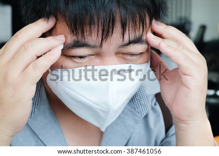 Portrait of a sick man with face mask. Headache. - stock photo