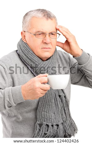 Portrait of a sick mature man holding a cup of tea and gesturing headache isolated on white background