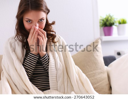Portrait of a sick woman blowing her nose while sitting on the sofa  - stock photo