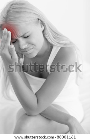 Portrait of a sick woman sitting on her bed - stock photo