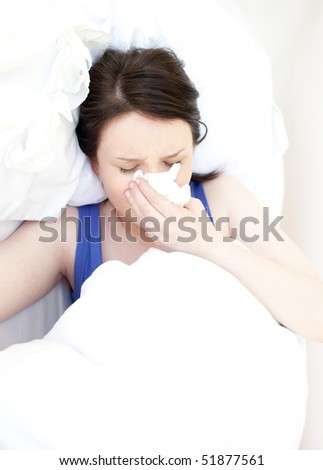 Portrait of a sick young woman relaxing in her bed - stock photo