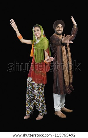 Portrait of a Sikh couple dancing - stock photo