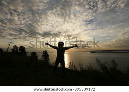 Portrait of a silhouette of a man on the river bank at sunset background