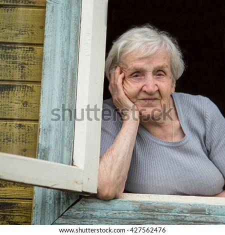 Portrait of a Slavic grandmother looking out the window of his house. - stock photo