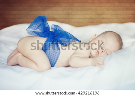 portrait of a sleeping child with a small blue bow - stock photo