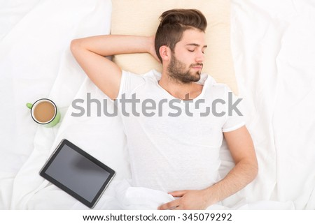 Portrait of a sleeping man from above with coffee.