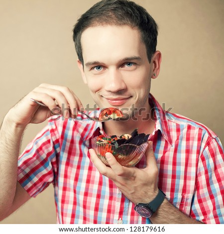 Portrait of a slim handsome boy eating salad over wooden background. Studio shot - stock photo
