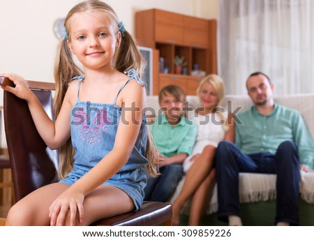 Portrait of a small and cheerful girl with her family at home - stock photo