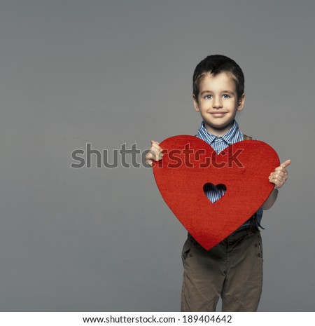 Portrait of a small boy presenting heart   - stock photo