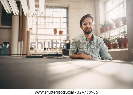 Portrait of a small business owner sitting casually in his worskhop studio looking confident and positive - stock photo