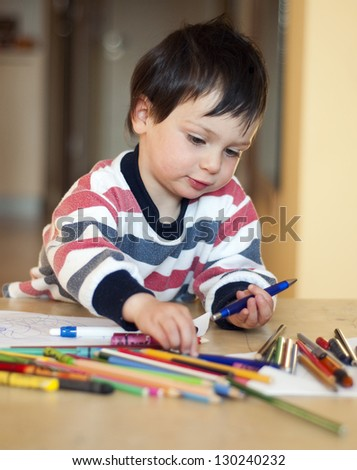 Portrait of a small child, boy or girl, drawing and playing with colorful crayons, pens and pencils. - stock photo