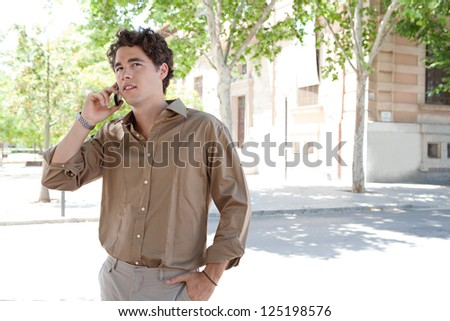 "Portrait of a smart businessman having a phone conversation on his ""smart phone"" while standing near a classic office building in the city. - stock photo"