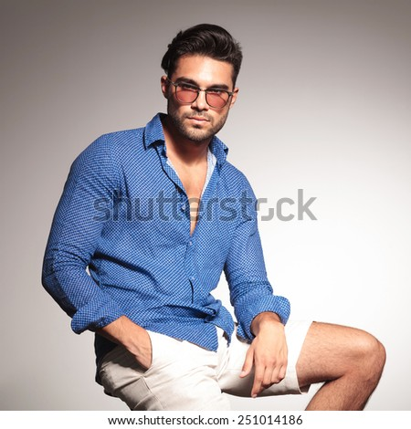 Portrait of a smart casual young man sitting while holding one hand in his pocket, looking at the camera. - stock photo