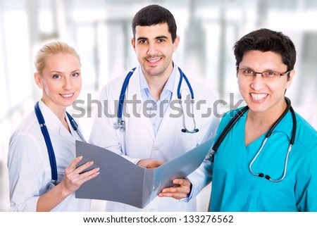 Portrait of a smart doctor sitting in front of his team and smiling