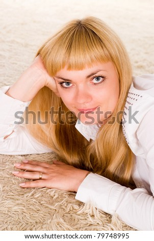portrait of a smart girl lying on a carpet