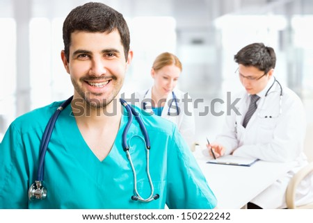 Portrait of a smart male doctor sitting in front of his team and smiling