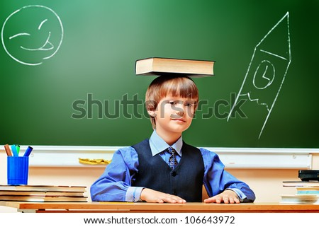 Portrait of a smart schoolboy in a classroom. - stock photo