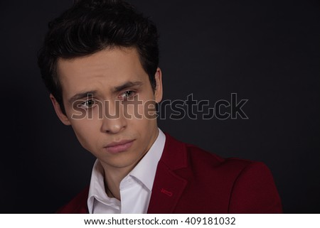 Portrait of a smart serious young man in suit  standing against black background - stock photo