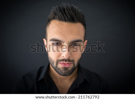 Portrait of a smart serious young man standing against blue background