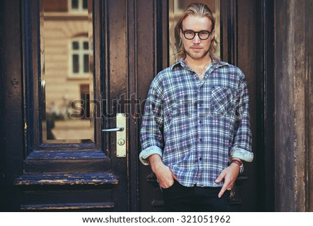 Portrait of a smart serious young man standing against building. Long blond hair - stock photo