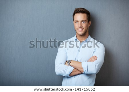 Portrait of a smart smiling young man standing against gray background - stock photo