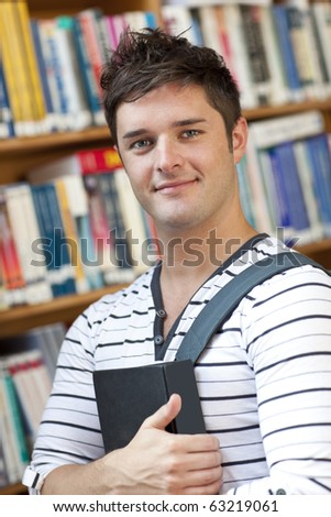 Portrait of a smart student holding a book standing in the library of his university - stock photo