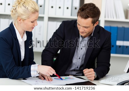 Portrait of a smart young businessteam looking at graphs sitting at office desk - stock photo